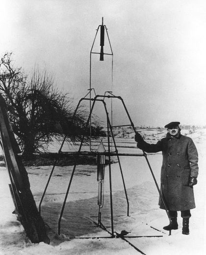 A photo of Robert Goddard and his first liquid-fueled rocket